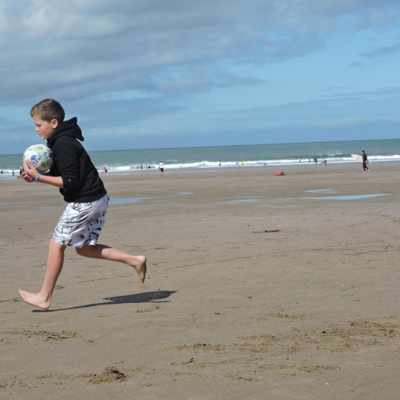 Boy running with rugby ball on the sandy beach