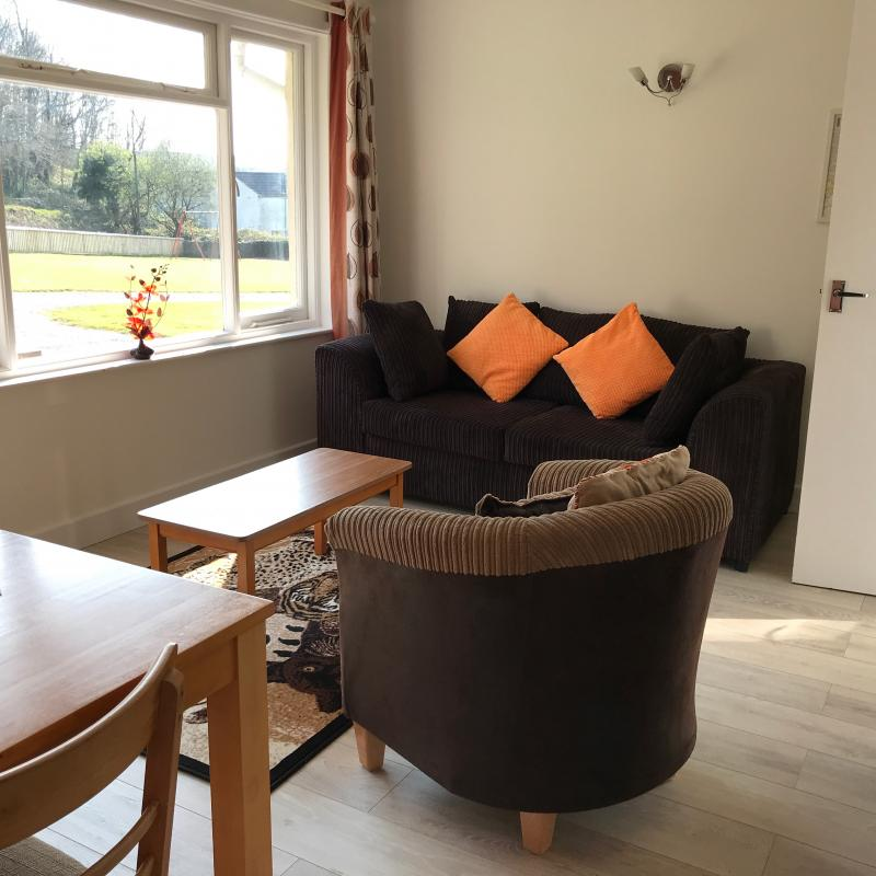 Begonia Lounge showing 3 seater sofa, wood laminate floor and tub chair