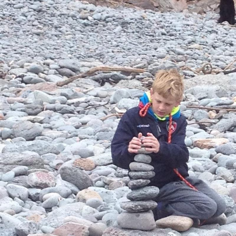 Young boy making a rock sculpture at Heddon's Mouth