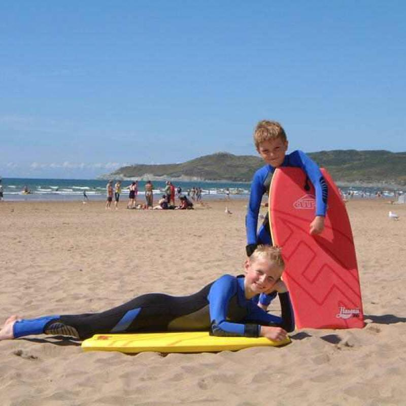 2 boys with body boards on sandy Woolacombe Beach