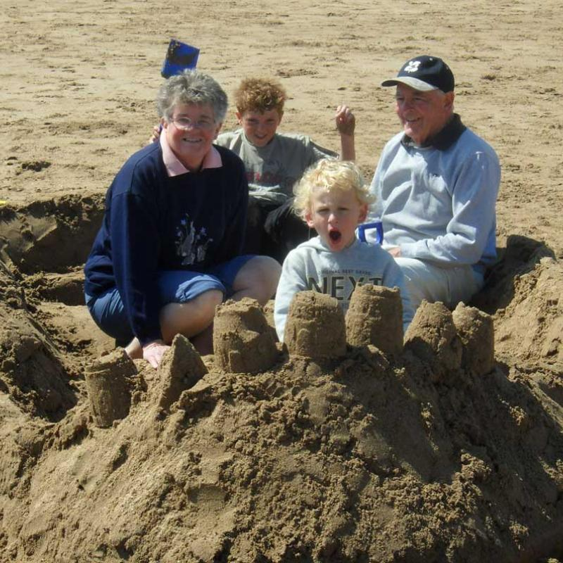 family sitting in a sand fire engine